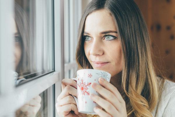 Portrait am Fenster mit Teetasse in der Hand